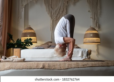 Attractive senior woman working out standing in Uttanasana at home. Full length