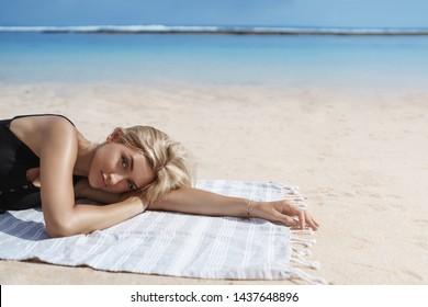 Attractive sensual blond tanned woman lie down beach blanket near ocean shore, seaside smiling camera sunbathing wear bikini relaxing summer vacation, travelling tropical paradise