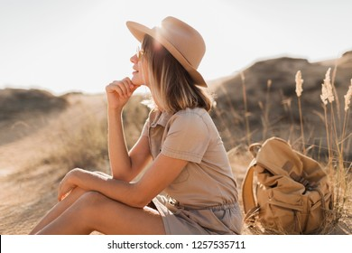 attractive sensual young woman in khaki dress in desert, treveling in Africa on safari, wearing hat and backpack, exploring nature, hot summer day, sunny weather