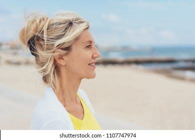 Attractive serious blond woman profile portrait as she stands on a sandy beach looking out over the ocean with a thoughtful expression
