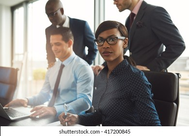 Attractive serious businesswoman wearing eyeglasses and blue blouse sitting at conference table with three male co-workers in front of large bright window