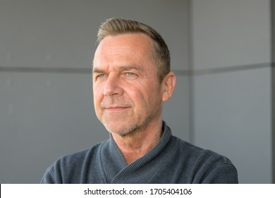Attractive serious trendy middle-aged man in grey sweater standing in the corner angle of a room looking thoughtfully at the camera with an intense stare