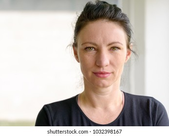 Attractive serious woman standing indoors looking pensively at the camera with a contemplative expression with copy space alongside