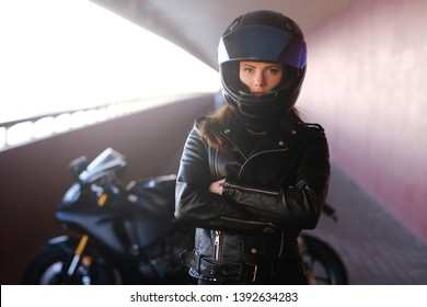 Attractive serious woman is standing next to her motobike crossing hands. She is wearing helmet and leather jacket.