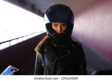 Attractive serious woman is standing next to her motobike. She is wearing a helmet.