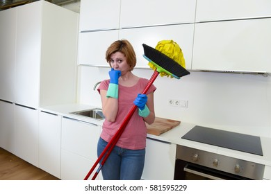 attractive service woman or housewife at home kitchen in gloves holding cleaning broom and mop frustrated and overworked looking tired busy in housework stress and housekeeping concept