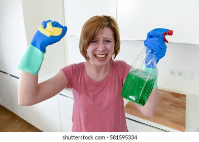 attractive service woman or housewife at home kitchen in gloves holding cleaning scourer and detergent spray bottle crying frustrated and overworked and busy desperate in housework stress