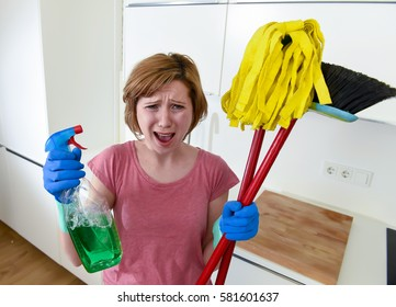 attractive service woman or housewife at home kitchen in gloves holding cleaning broom and mop and spray bottle frustrated and overworked and busy desperate in housework stress
