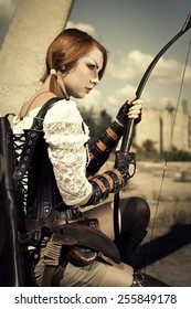 Attractive severe redhair woman warrior holding in her hands bow and arrow on the industrial background.