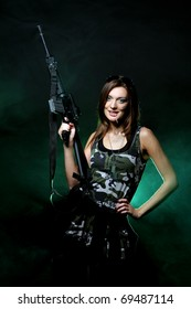 Attractive and sexy army girl with assault rifle in sunglasses
