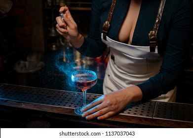 Attractive sexy barmaid with deep neckline spraying blue-colored bitter on the elegant cocktail glass on the bar counter