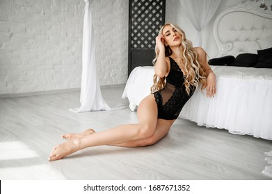 Attractive and sexy blonde in a black lace bodysuit in a bedroom