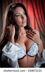 attractive and sexy brunette with white bra .Portrait of young sensual woman wearing white bra in classic boudoir scene.Beautiful and sexy girl with long hair wearing white lingerie in vintage room