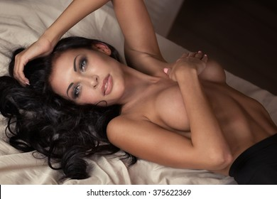 Attractive sexy brunette woman lying in bed, looking at camera. Girl naked.
