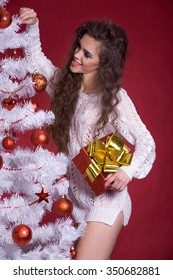 Attractive sexy girl at Christmas with gifts