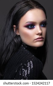 Attractive sexy girl with colorful smoky eyes, perfect skin, black hair and cat's eyes makeup.