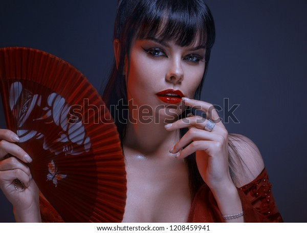 attractive sexy girl with dark black hair, gray eyes, amazing makeup with red lips looks playfully at the camera. wearing a maroon light, loose dress with open shoulders, holds a fan