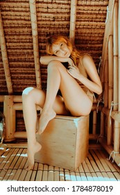 Attractive sexy girl with ginger hair posing in Bali Style Bamboo Bungalow during her visit to Bali, Indonesia. Red haired woman with Charming Appearance
