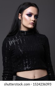 Attractive sexy girl with professional evening makeup, perfect shining skin, black hair and cat's eyes. Black clothes.