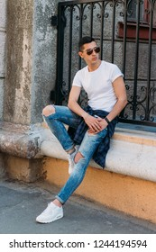 Attractive, sexy guy sits leaning on a curb on a ledge in the wall on the street in sunglasses. self-confidence, flatulence and arrogance.model, posing, portrait of a young man