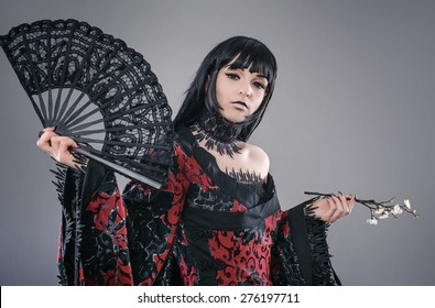 Attractive and sexy lady with hand fan. Isolated on a gray background. Studio shot