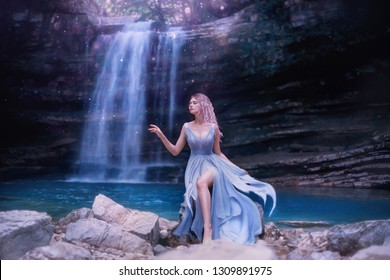 attractive sexy water fairy with sad face, fantastic nymph near lake in Georgia, Martvili Canyon nature. tender girl with long blue flying dress, pink hair. creative art processing, creative colors