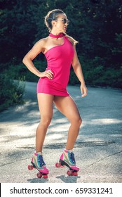 Attractive sexy woman in 30s standing on asphalt wearing bright neon pink dress and roller skates. Toned image.