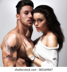 Attractive sexy woman leaning on the bare chest of attractive young brunette man. Fashion photo.
