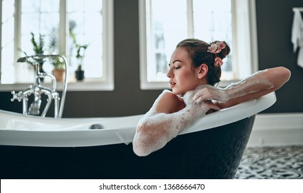 Attractive sexy woman lying naked in bath full of foam in modern bathroom. Beauty concept.