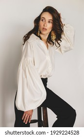 Attractive sexy woman wear business look. Girl look surprised and look at back. Brunette model wear white shirt, gold earrings and black pants. Winter, fall autumn or spring minimal outfit.