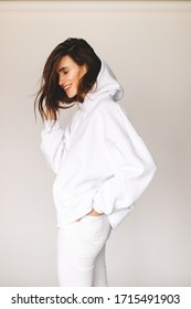 Attractive sexy woman wear white total look. Girl look sexy and happy. Elegant look. Brunette model wear white hoody and jeans. Winter, fall autumn or spring minimal outfit. Woman is positive.
