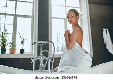 Attractive sexy woman in white towel in bathroom. Beauty concept.