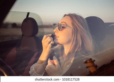Attractive and sexy young blonde woman prepares for night out, applies make up and red lipstick looking into rearview mirror at reflection. Concept fashion, vintage and youth, date evening