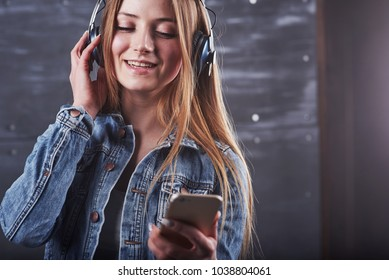 Attractive sexy young woman in jeans jacket is posing in the studio listens to music in headphones.