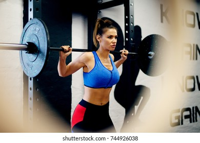 Attractive shape woman exercise with a barbell in the modern gym.