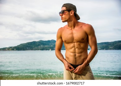 Attractive shirtless athletic young man on beach by the sea, with baseball cap and sunglasses, looking away