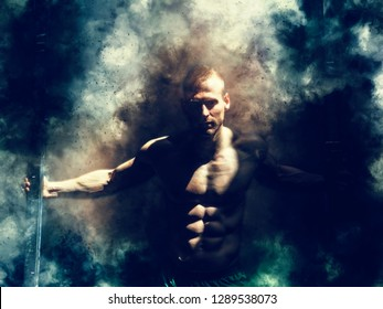 Attractive shirtless blond male bodybuilder in shorts indoors in dark room with smoke, showing muscular torso and ripped abs