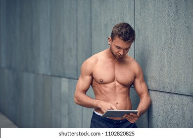 Attractive shirtless fit muscular young man leaning against an urban wall working on a tablet pc