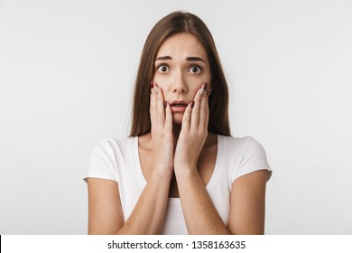 Attractive shocked young woman standing isolated over white background