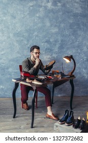 attractive shoeshine boy reparing shoes indoors, full length photo.art concept