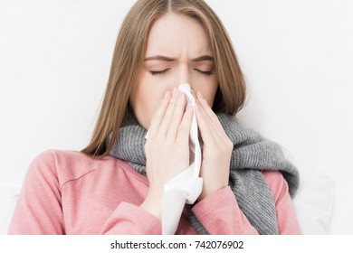 attractive sick girl wiping nose and lying in bed at home