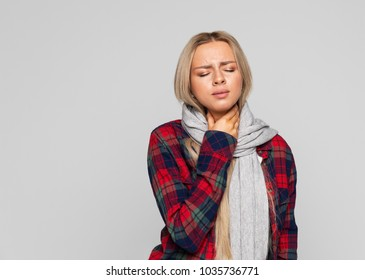 Attractive sick young blonde woman in checked shirt, wrapped scarf having sore throat, holding hand on her neck/ Throat pain, painful swallowing concept/ Inflammation of the upper respiratory tract
