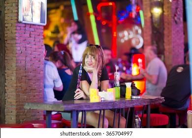Attractive single woman smoking shisha and drinking at bar alone