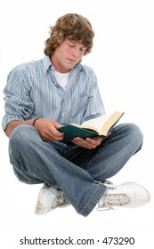 Attractive Sixteen Year Old Teen Boy reading book in casual over white background.  Light brown curly hair and hazel eyes.