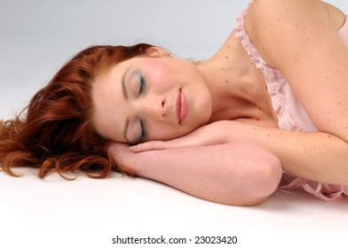 The attractive sleeping redhead women in pink slip.
