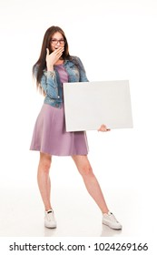 Attractive slender girl posing with a white sign. Dressed in a pink dress and dinsevuyu jacket, sneakers and glasses. Long hair. Isolated photo on a white background. To use advertising, logo