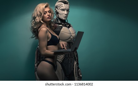 Attractive slender sexy blonde girl wearing black underwear holding laptop showing to a robotic man the screen, couple against bluish background