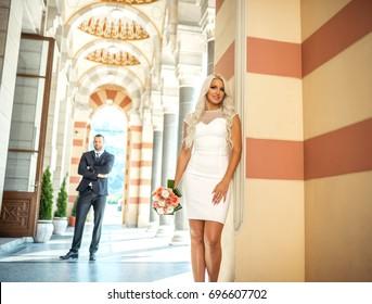 Attractive slim fit wedding couple posing at Sarajevo City Hall.  Bride in focus. Toned image.