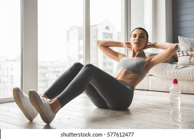 Attractive slim girl in sportswear is doing abs exercises on the floor at home
