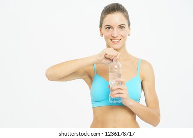 Attractive slim girl in sportswear with a smile opens a plastic bottle with clean water during a workout on a white background. Hydration and thirst. Sport exercises. Isolated on white background.